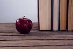 Apple and books arranged on wooden table. Against white background stock photography