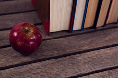 Apple and books arranged on wooden table. Close-up of apple and books arranged on wooden table stock image