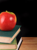 Apple and books for back to school. A red apples sits on top of three old hardcover books with a blackboard background with copy space Stock Photo