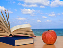 Apple and books on desk. Red apple and books on desk royalty free stock photography