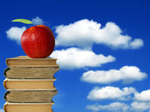 Apple on books heap. Against cloudy blue sky Royalty Free Stock Image