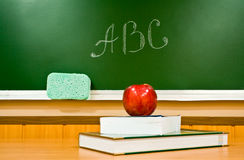 Apple, books and letters. Juicy apple and book at school on a background a board Stock Photo