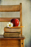 Apple and books on old school chair Stock Photo