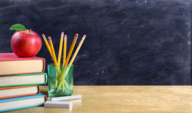 Apple on books with pencils and empty blackboard Stock Image
