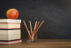 Apple on books with pencils and empty blackboard - back to school. Apple on books with pencils and empty blackboard - chalk Royalty Free Stock Images