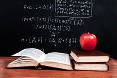 Apple and books on a wooden table and school blackboard with mathematical equations in the classroom Stock Photography
