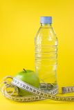 Apple, bottle and centimeter. Green apple with centimeter and bottle on yellow background Stock Images