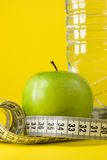 Apple, bottle and centimeter. Green apple with centimeter and bottle on yellow background Royalty Free Stock Images