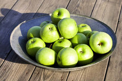 Apple Bowl. Green apples in metal bowl on wooden floor stock images