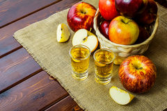 Apple brandy shots and red apples. In the rustic wicker basket on wooden background Stock Photos