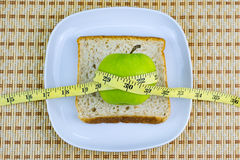 Apple and bread served on white plate with measuring tape. Royalty Free Stock Photo