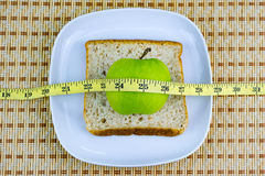 Apple and bread served on white plate with measuring tape. Royalty Free Stock Images