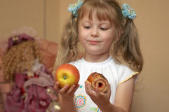 Apple or cake. A girl holding an apple and a cake Stock Photography