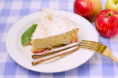Apple cake for breakfast. A piece of apple sponge cake with cinnamon and mint on a checkered tablecloth stock image