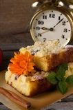 Apple cake with bright bloom on brown paper. Vertical photo with few slices of apple cake with raisins, marigold bloom and melissa on brown paper with spices stock photo