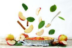 Apple cake with flying ingredients to bake it Royalty Free Stock Images