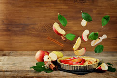 Apple cake with flying ingredients to bake it Stock Images
