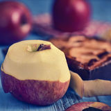 An apple cake and some apples on a blue table. Closeup of an apple cake and some red apples on a blue rustic wooden table, with a filter effect Royalty Free Stock Photography