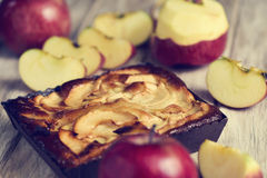 An apple cake and some apples on a wooden table. Closeup of an apple cake and some red apples on a rustic wooden table royalty free stock photos