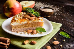 Apple cake with whipped cream, caramel and almond topping. Delicious cake with apple and whipped cream filling, topped with caramel and almond royalty free stock image