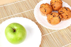 Apple and cakes on white plates Royalty Free Stock Photos