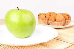 Apple and cakes in white plates on wooden mat Stock Images