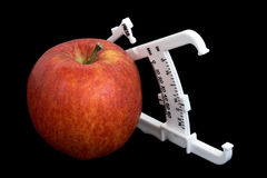 Apple and Calipers Over Black. An apple and bodyfat calipers isolated over a black background Royalty Free Stock Photos