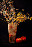 Apple,candle, and vase of flowers on black background Royalty Free Stock Photos