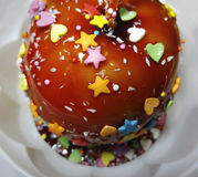 Apple in a caramel glaze. Strew of hearts stars balls. Apple close-up in  white plate. Stock Photos