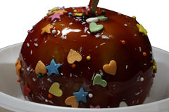 Apple in a caramel glaze. Strew of hearts stars balls. Apple close-up in white plate isolated on white background. Stock Photos