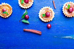 Apple caramel little tarts on blue rustic background. French tatin with paradise apple. Top view. Frame. Copy space. Stock Photos