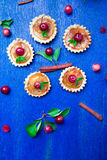 Apple caramel little tarts on blue rustic background. French tatin with paradise apple. Top view Stock Photography