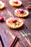 Apple caramel little tarts on brown rustic background. French tatin with paradise apple. Stock Photo
