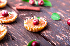 Apple caramel little tarts on brown rustic background. French tatin with paradise apple. Stock Image