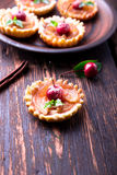 Apple caramel little tarts on brown rustic background. French tatin with paradise apple. Royalty Free Stock Photo