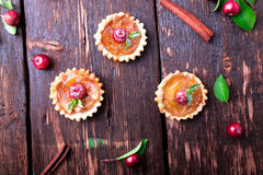 Apple caramel little tarts on brown rustic background. French tatin with paradise apple. Top view. Stock Images