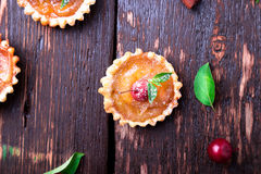 Apple caramel little tarts on brown rustic background. French tatin with paradise apple. Top view. Stock Image
