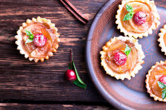 Apple caramel little tarts on brown rustic background. French tatin with paradise apple. Top view. Royalty Free Stock Photos