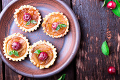 Apple caramel little tarts on brown rustic background. French tatin with paradise apple. Top view. Stock Photo