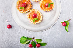 Apple caramel little tarts on grey background. French tatin with paradise apple. Top view. Stock Photos