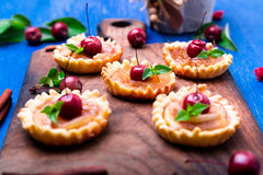 Apple caramel little tarts on wooden board and blue rustic background. French tatin with paradise apple. Close up. Royalty Free Stock Photo