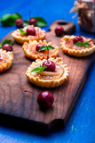 Apple caramel little tarts on wooden board and blue rustic background. French tatin with paradise apple. Close up. Stock Photography