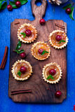 Apple caramel little tarts on wooden board and blue rustic background. French tatin with paradise apple. Top view Stock Photo