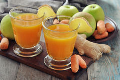 Apple and carrot juice with ginger. Apple and carrot juice in glass with ginger,  fresh vegetables and fruits on wooden background Royalty Free Stock Photo