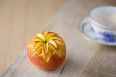 Apple carved with a cup of tea. Apple carved on a wooden board with a white and blue cup of tea Stock Photo