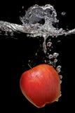 Apple cayó en el agua con el chapoteo Imagen de archivo libre de regalías