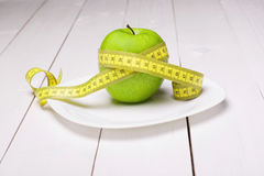 Apple with centimeter on the plate. Healthy eating. Eat Royalty Free Stock Photography