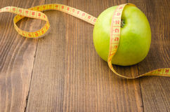 Apple and centimeter with wood background. Fitness background with apple and centimeter Stock Images