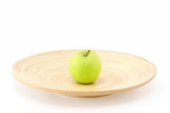 Apple in the centre of plate. One apple in the centre of wooden plate Stock Photo