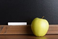 Apple and chalk in front of a chalkboard Royalty Free Stock Image